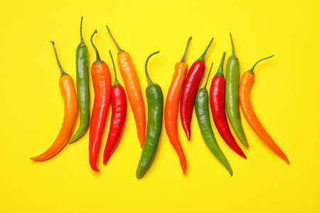 Different hot chili peppers on yellow background, flat lay Stock Photo