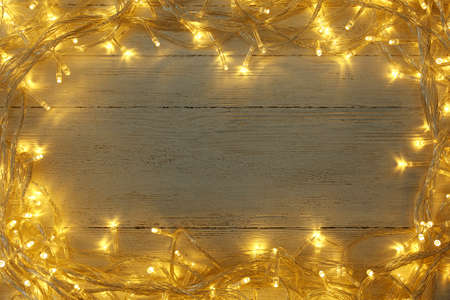 Frame made of glowing Christmas lights on white wooden background, top view. Space for text