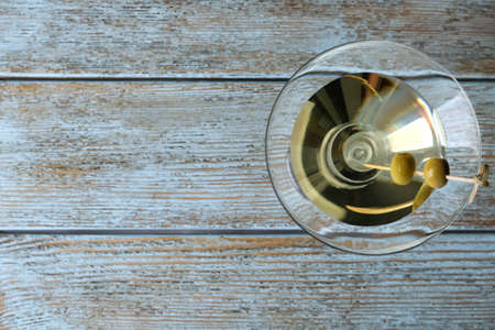 Glass of Classic Dry Martini with olives on wooden table, top view. Space for text