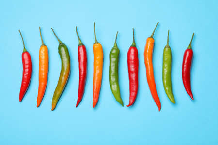 Different hot chili peppers on blue background, flat lay