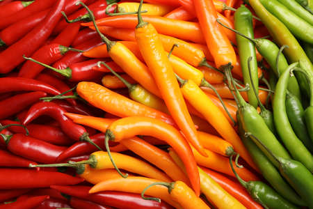 Different ripe chili peppers as background, top view