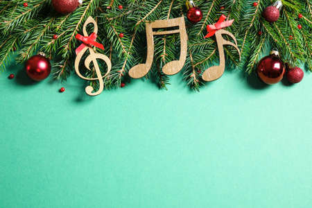 Flat lay composition with Christmas decor and music notes on light green background, space for text Фото со стока