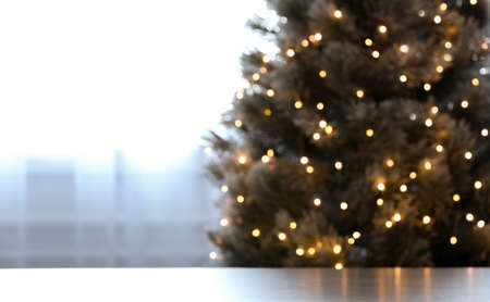 Blurred view of beautiful Christmas tree with yellow lights near window indoors, focus on table. Space for text 스톡 콘텐츠