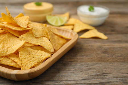 Plate of Mexican nacho chips on wooden table, closeup. Space for text