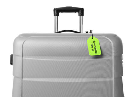 Grey suitcase with TRAVEL INSURANCE label on white background 스톡 콘텐츠