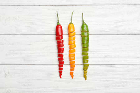 Different cut chili peppers on white wooden table, flat lay