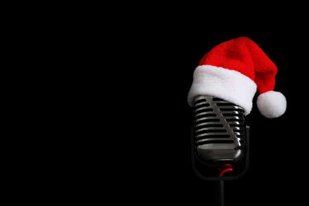 Microphone with Santa hat on black background, space for text. Christmas music Standard-Bild