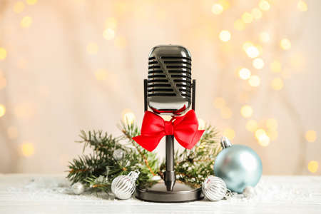 Microphone with red bow and decorations on white table against blurred lights. Christmas music Stock Photo