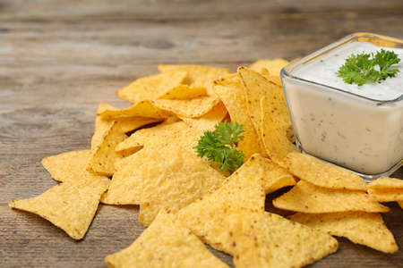 Mexican nacho chips with sauce on wooden table