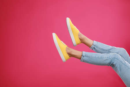 Woman in stylish sport shoes on pink background. Space for text Archivio Fotografico - 129586811