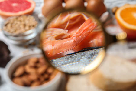 Different products with magnifier focused on shrimps and fish, closeup. Food allergy concept Stock Photo