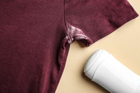 Clothes with stain and deodorant on beige background, closeup