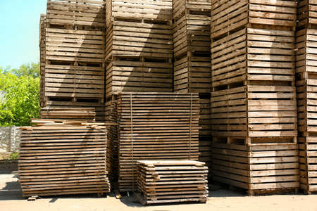 Pile of empty wooden crates outdoors on sunny day Stock Photo
