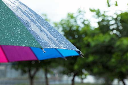 Colorful umbrella outdoors on rainy day, closeup