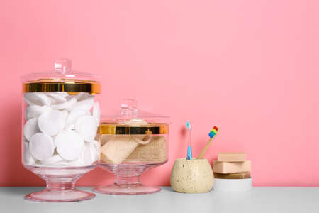 Composition of glass jar with cotton pads on table near pink wall. Space for text