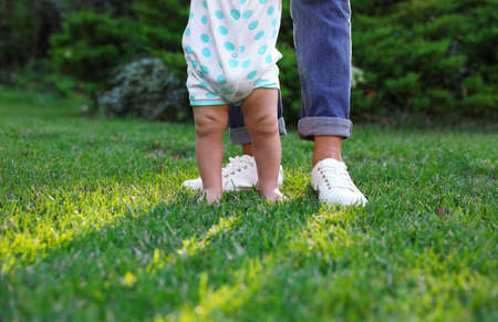 Cute little baby learning to walk with his nanny on green grass outdoors, closeup
