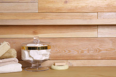 Composition of glass jar with cotton pads on table near wooden wall. Space for text 写真素材 - 129592092