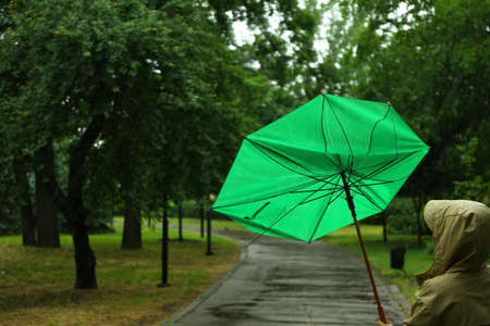 Woman with broken green umbrella in park on rainy day