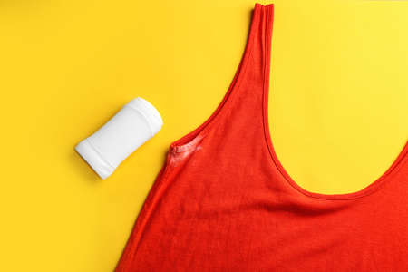 Clothes with stain and deodorant on yellow background, top view Stock Photo