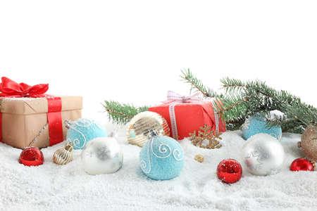 Rami di abete, decorazioni natalizie e neve su sfondo bianco