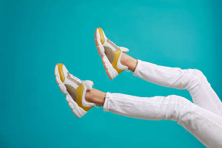 Woman in stylish sport shoes on light blue background Archivio Fotografico - 129594891