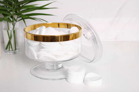 Glass jar with cotton pads on table in bathroom 写真素材 - 129595083