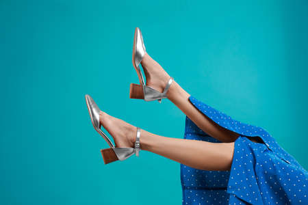 Woman in stylish shoes on light blue background Archivio Fotografico - 129595084