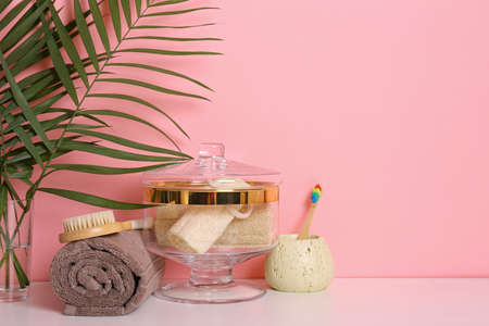 Composition of glass jar with luffa sponges on table near pink wall. Space for text 写真素材 - 129595693