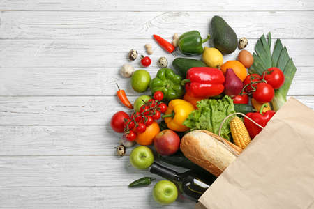Paper bag with different groceries on white wooden table, flat lay. Space for text