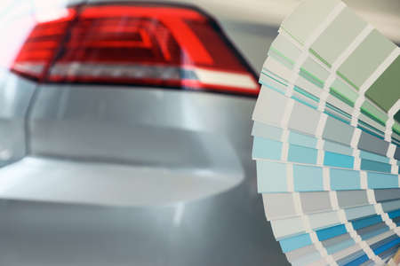 Palette with different color samples near modern car, closeup. Space for text