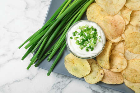 Sour cream and chips on white marble table, flat lay