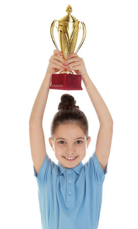 Happy girl in school uniform with golden winning cup isolated on white
