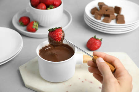 Woman dipping strawberry into fondue pot with chocolate at grey table, closeup
