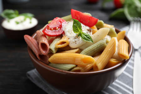 Delicious vegetable pasta with sour cream dressing on black wooden table, closeup 写真素材