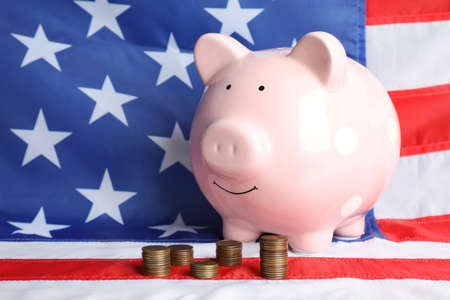 Piggy bank and stacks of coins on USA national flag Foto de archivo