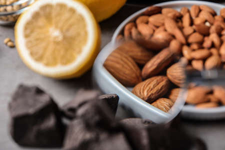 Different products with magnifier focused on almonds, closeup. Food allergy concept