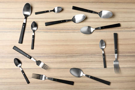 Frame made of new cutlery on wooden table, flat lay with space for text Stockfoto