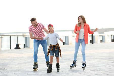 Happy family roller skating on city street