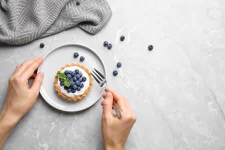 Woman eating blueberry tart at marble table, top view with space for text. Delicious pastries