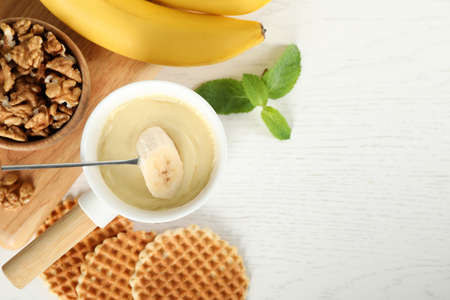 Dipping slice of banana into fondue pot with white chocolate on wooden table, top view. Space for text Banque d'images