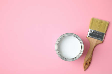 Open can with white paint and brush on pink background, flat lay. Space for text