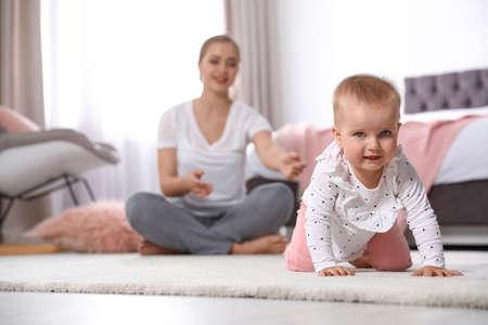 Mother watching her baby crawl on floor in bedroom