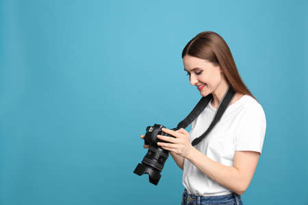 Fotografo professionista con fotocamera moderna su sfondo azzurro. Spazio per il testo Archivio Fotografico