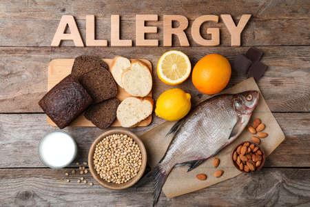 Composizione piatta con vari alimenti e parola allergia fatta di lettere su tavola di legno wooden Archivio Fotografico