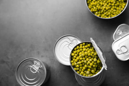 Tin cans and green peas on grey table, top view with space for text Stock Photo