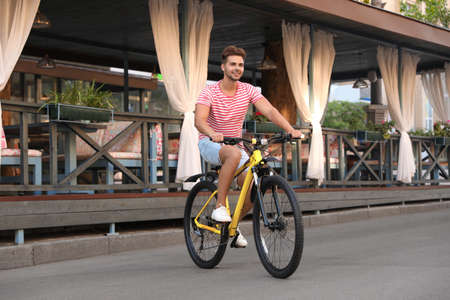 Handsome young man riding bicycle on city street