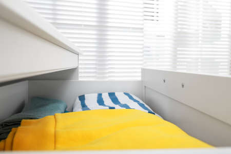 Modern open chest of drawers with clothes in room, closeup