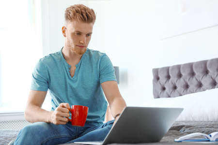 Young man using laptop while sitting on bed at home