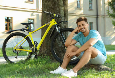 Handsome young man sitting near bicycle on green grass