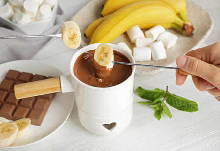 Woman dipping banana into fondue pot with chocolate at white wooden table, closeup Stock Photo